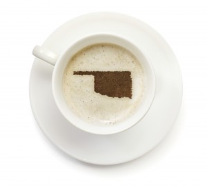 A top shot of a cup of coffee with froth and powder in the shape of Oklahoma (USA).(series) How about having a break :)